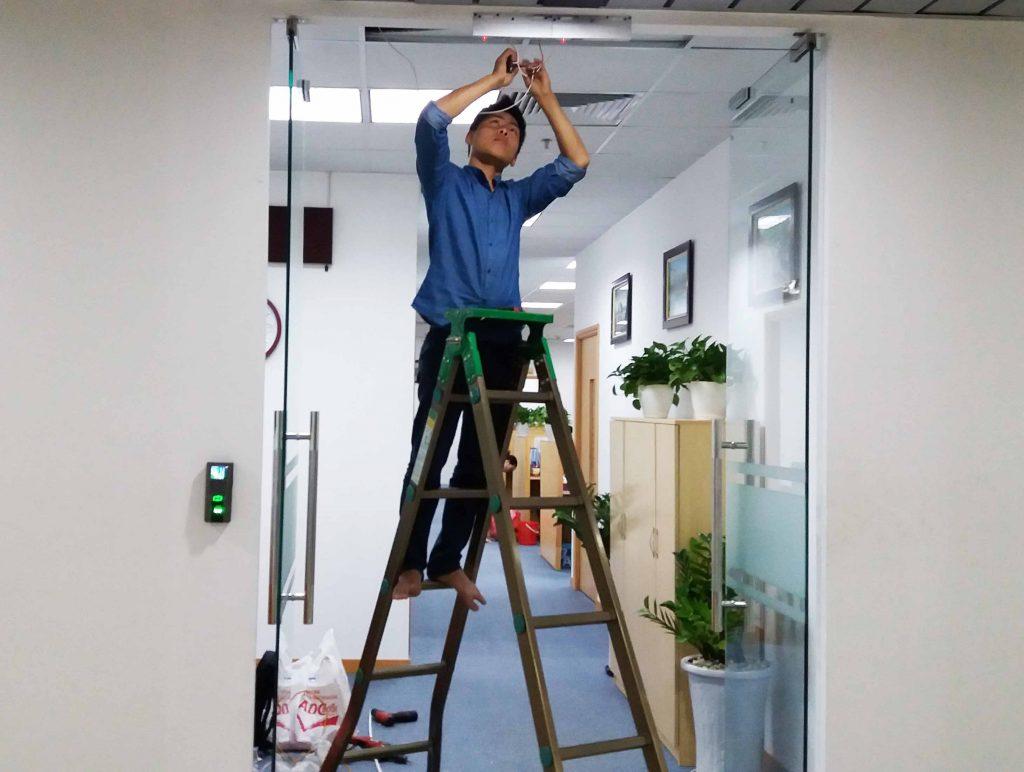 Nhân viên đang tiến hành lắp đặt thiết bị kiểm soát cửa ra vào